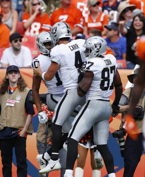 Oakland Raiders wide receiver Seth Roberts (10) celebrates his touchdown with quarterback Derek Carr (4) and tight end Jared Cook (87) during the second half of an NFL football game against the Denver Broncos, Sunday, Sept. 16, 2018, in Denver. (AP Photo/Jack Dempsey)