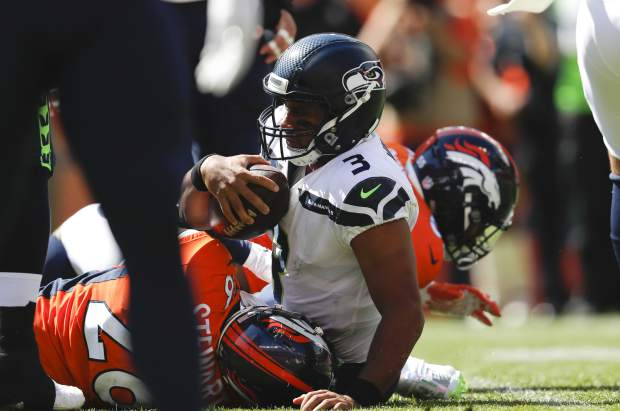 Seattle Seahawks quarterback Russell Wilson, center, is sacked by Denver Broncos linebacker Bradley Chubb, right, and defensive back Darian Stewart, left, during the first half of an NFL football game Sunday, Sept. 9, 2018, in Denver. (AP Photo/David Zalubowski)