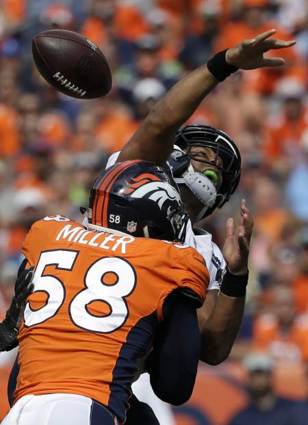 Seattle Seahawks quarterback Russell Wilson, above, loses the ball as he is hit by Denver Broncos linebacker Von Miller (58) during the first half of an NFL football game Sunday, Sept. 9, 2018, in Denver. The Seahawks recovered the ball on the play. (AP Photo/Jack Dempsey)