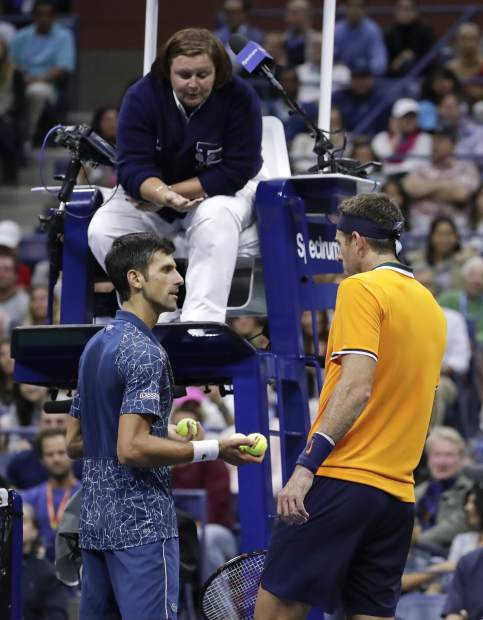 Novak Djokovic, of Serbia, left, talks with Juan Martin del Potro, of Argentina, as chair umpire Alison Hughes listens during the men's final of the U.S. Open tennis tournament, Sunday, Sept. 9, 2018, in New York. (AP Photo/Julio Cortez)