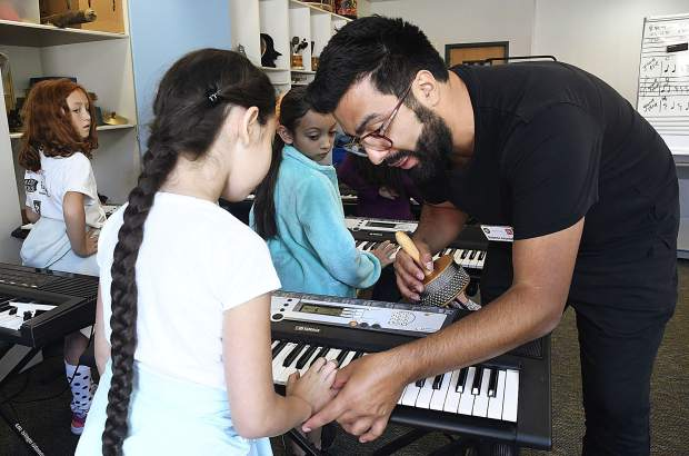 AmeriCorps ArtistYear Fellow Roberto Arundale works with third-graders on the keyboard during David Parker's music class at Sopris Elementary.