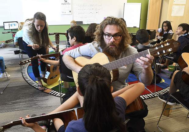 AmeriCorps ArtistYear Fellow Henry Bayless shows a students how to play a chord as he helps Glenwood Elementary School music teacher Emma Leake teach fourth-graders how to play the guitar.