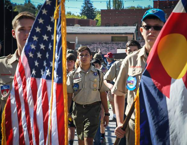 Members of Boy Scout Troop 225 lead the parade across the Grand Avenue pedestrian bridge during Saturday's 125th Big Birthday Bash at the Hotel Colorado.