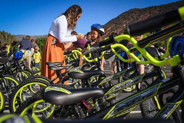 Sopris Elementary School Family Liaison Betty Lucas helps second-grader Monika Mireles put her nametag on her brand new bike provided by Wish for Wheels on Tuesday morning.