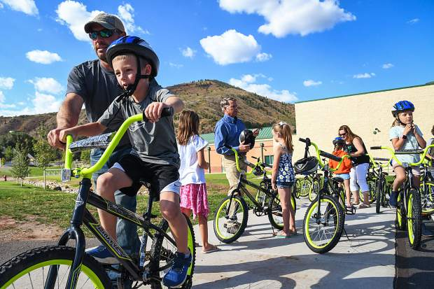 Sopris Elementary School second-grader Ladson Whitaker gets help riding away on his brand new bike at the school on Tuesday morning. Wish for Wheels provided 68 bikes for all second-graders at Sopris Elementary and another 127 bikes for second-graders at Riverview School and Glenwood Springs Elementary School. Wish for Wheels will head to Wamsley and Highland Elementary Schools in Rifle on Thursday.