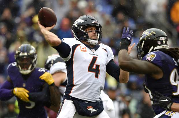 Denver Broncos quarterback Case Keenum, center, throws a pass as he is pressured by Baltimore Ravens linebacker Za'Darius Smith, right, in the first half of an NFL football game, Sunday, Sept. 23, 2018, in Baltimore. (AP Photo/Gail Burton)