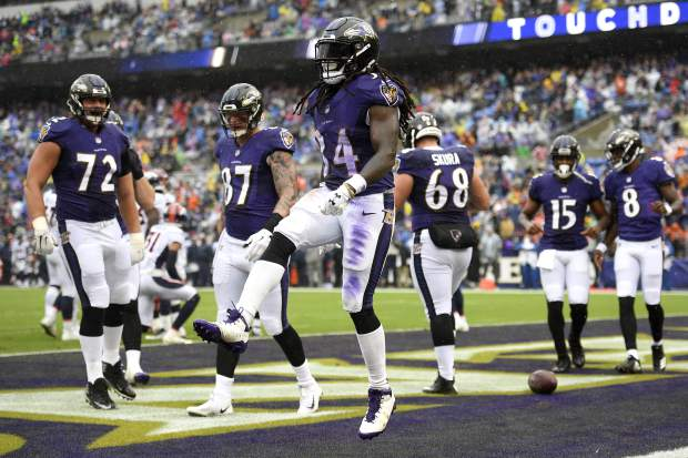 Baltimore Ravens running back Alex Collins, center, celebrates his touchdown in the first half of an NFL football game against the Denver Broncos, Sunday, Sept. 23, 2018, in Baltimore. (AP Photo/Nick Wass)