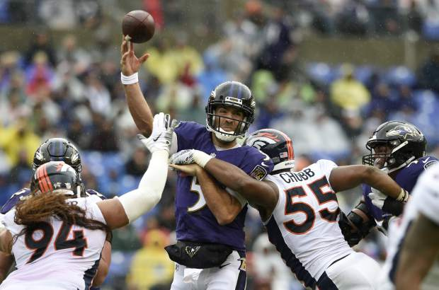 Baltimore Ravens quarterback Joe Flacco, center, throws a pass as he is pressured by Denver Broncos defensive tackle Domata Peko Sr. (94) and linebacker Bradley Chubb (55) in the first half of an NFL football game, Sunday, Sept. 23, 2018, in Baltimore. (AP Photo/Gail Burton)