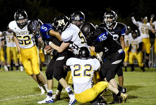 Coal Ridge quarterback is swallowed up by Meeker defenders Brayden Woodward (55) and Tevin Pelloni on 4th and 10 in overtime Friday in New Castle. The Titans fell to the Cowboys 22-14 in their season opener.