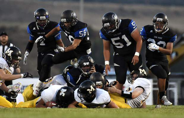 The Coal Ridge defense scrambles for the loose ball after Titans defensive tackle Damian Spell created a fumble while sacking Meeker quarterback Ryan Phelan in the second quarter.