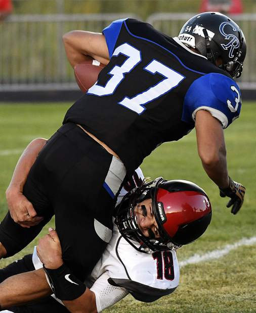 Coal Ridge's Moises Contreras gets thrown to the ground by Paonia's Grey Neal during first quarter action Friday in New Castle. The Titans fell to the Eagles 19-0.