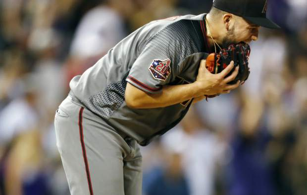 Arizona Diamondbacks relief pitcher Silvino Bracho bites his glove after giving up a three-run home run to Colorado Rockies' Trevor Story in the fifth inning of a baseball game Monday, Sept. 10, 2018, in Denver. (AP Photo/David Zalubowski)