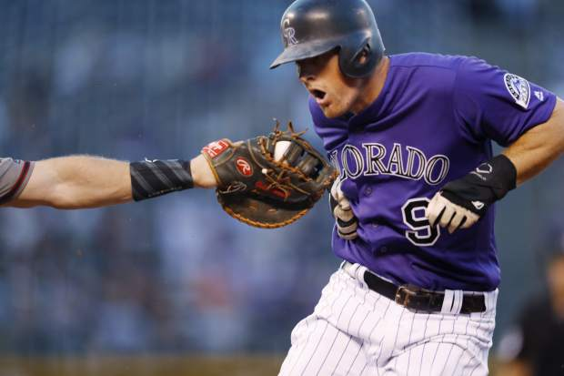 Arizona Diamondbacks first baseman Paul Goldschmidt, left, reaches out to put the tag on Colorado Rockies' DJ LeMahieu after he was caught in a rundown while trying to advance from first to second base in the first inning of a baseball game against the Monday, Sept. 10, 2018, in Denver. (AP Photo/David Zalubowski)