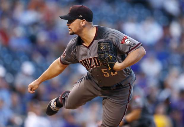 Arizona Diamondbacks starting pitcher Zack Godley works against the Colorado Rockies in the first inning of a baseball game against the Monday, Sept. 10, 2018, in Denver. (AP Photo/David Zalubowski)
