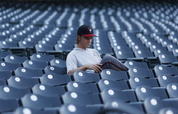 Arizona Diamondbacks starting pitcher Zack Greinke reads in the empty stands before a baseball game against the Colorado Rockies Monday, Sept. 10, 2018, in Denver. (AP Photo/David Zalubowski)