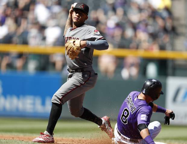 Arizona Diamondbacks second baseman Ketel Marte, left, throws to first base after forcing out Colorado Rockies' Gerardo Parra at second base on the front end of a double play hit into by Ian Desmond in the second inning of a baseball game Thursday, Sept. 13, 2018, in Denver. (AP Photo/David Zalubowski)