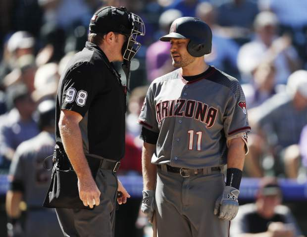 Arizona Diamondbacks' A.J. Pollock, right, confers with home plate umpire Chris Conroy after he called out Pollock on strikes to end the top of in the fourth inning of a baseball game against the Colorado Rockies Thursday, Sept. 13, 2018, in Denver. (AP Photo/David Zalubowski)