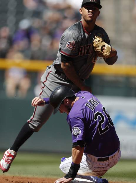 Arizona Diamondbacks shortstop Ketel Marte throws over Colorado Rockies' David Dahl after forcing him out at second base on the front end of a double play in the first inning of a baseball game Thursday, Sept. 13, 2018, in Denver. (AP Photo/David Zalubowski)