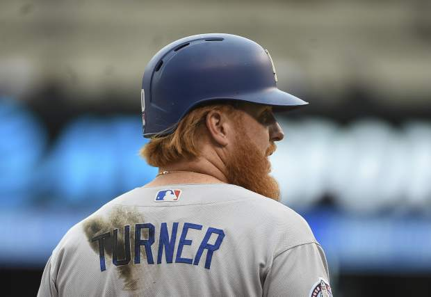 Los Angeles Dodgers baserunner Justin Turner looks on from third base during the eighth inning of a baseball game against the Colorado Rockies, Sunday, Sept. 9, 2018, in Denver. (AP Photo/John Leyba)