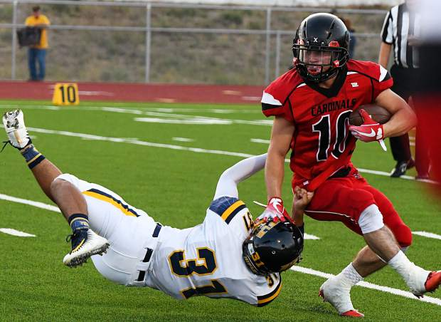 Grand Valley Cardinal Jonathan Pena stiff arms Rifle Bear Kevin Tlaxcala during Thursday night's game at Grand Valley High School.