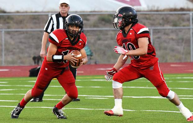 Grand Valley Cardinal Sam Gomez hands the ball off to Jonathan Pena during Thursday night's game against the Rifle Bears at Grand Valley High School.