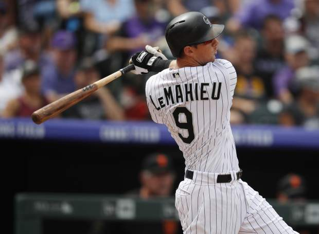 Colorado Rockies' DJ LeMahieu follows the flight of his two-run home run off San Francisco Giants starting pitcher Madison Bumgarner in the first inning of a baseball game Monday, Sept. 3, 2018, in Denver. (AP Photo/David Zalubowski)