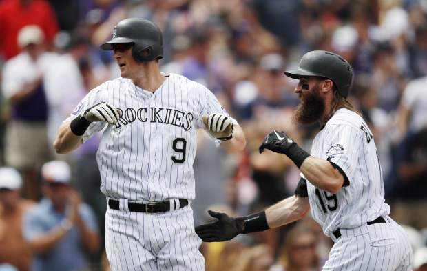 Colorado Rockies' DJ LeMahieu, left, celebrates hitting a two-run home run with Charlie Blackmon against the San Francisco Giants in the first inning of a baseball game Monday, Sept. 3, 2018, in Denver. (AP Photo/David Zalubowski)
