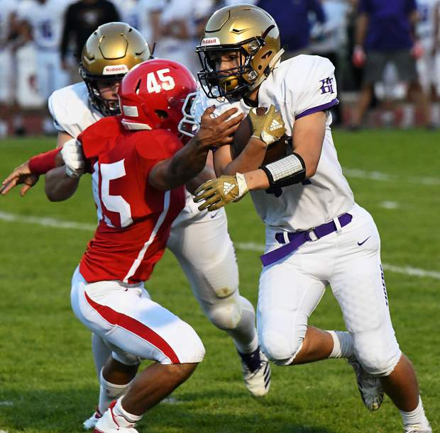 Holy Family Tiger Oscar Sena runs the ball past the defending Glenwood Springs Demon Joshua Sanchez during Friday night's game at Stubler Memorial Field.