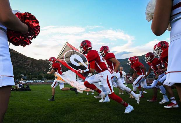 The Glenwood Springs Demons take to the field during the season opening game at Stubler Memorial Field on Friday night against the Holy Family Tigers.