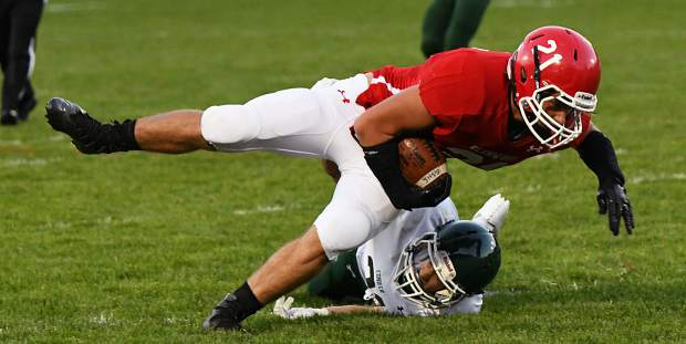 Glenwood Springs Demon Elliot Dwyer-Walz leaps forward to aboud the tackle during Friday night's game against the Conifer Lobos at Stubler Memorial Field.