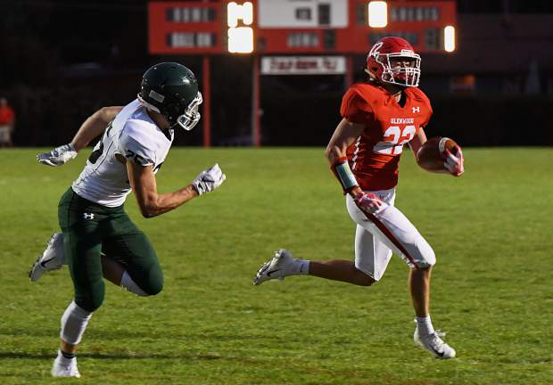 Glenwood Springs Demon Gavin Olson runs the ball past the defending Conifer Lobos to score a touchdown late in the first quarter during Friday night's game at Stubler Memorial Field.