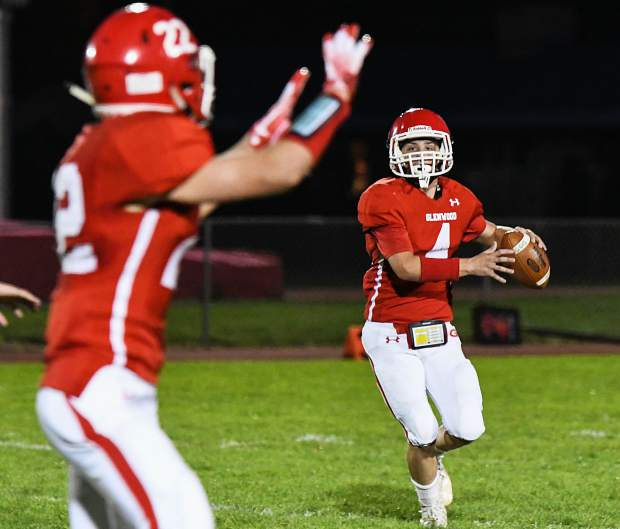 Glenwood Springs Demon quarterback Dylan Albright looks to pass the ball to the receiving Demon Gavin Olson during Friday night's game against the Conifer Lobos at Stubler Memorial Field.