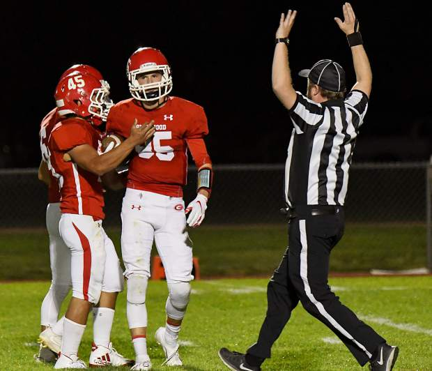 Glenwood Springs Demons celebrate at Wyatt Ewer comes up with the interception late in the first half against the Conifer Lobos on Friday night at Stubler Memorial Field.