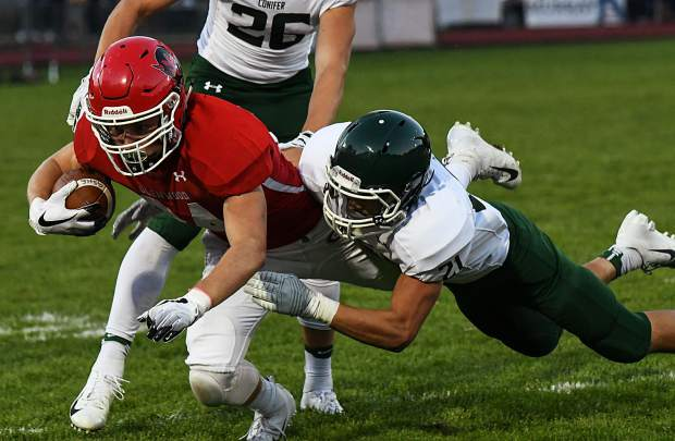 Glenwood Springs Demon Luke Gair lunges forward while Conifer Lobo Stephen Douglas makes the tackle during Firday night's game at Stubler Memorial Field.