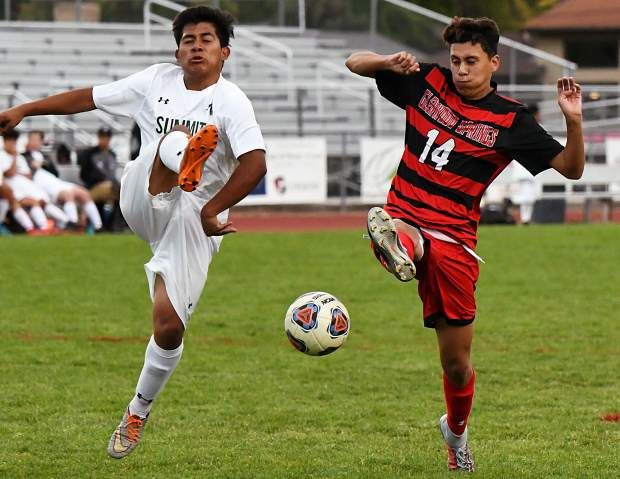 Glenwood Springs Demon German Alvarado and Summit Tiger Erick Hernandez battle for the ball in the goalbox during Thursday night's game at Stubler Memorial Field.