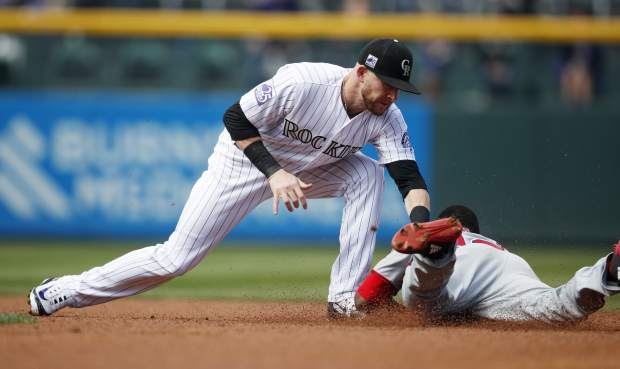 Colorado Rockies shortstop Trevor Story, left, applies the tags to put out Washington Nationals' Victor Robles as he tries to steal second base in the first inning of a baseball game Sunday, Sept. 30, 2018, in Denver. (AP Photo/David Zalubowski)