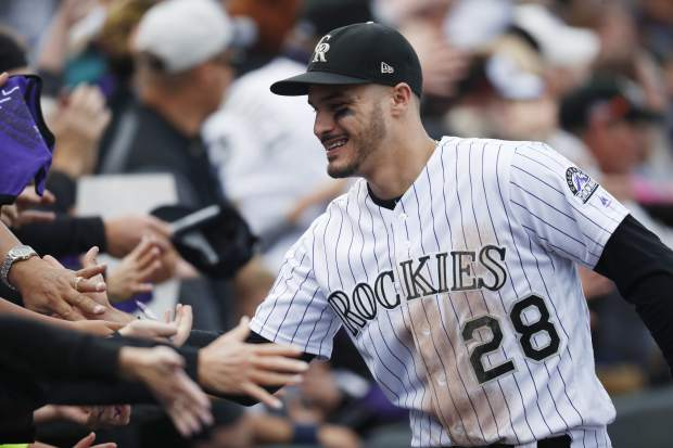 Fans congratulate Colorado Rockies third baseman Nolan Arenado after the ninth inning of a baseball game against the Washington Nationals Sunday, Sept. 30, 2018, in Denver. The Rockies won 12-0. (AP Photo/David Zalubowski)
