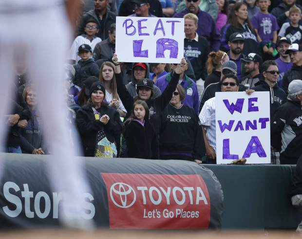 Fans hold up signs in the ninth inning of a baseball game as the Colorado Rockies host the Washington Nationals Sunday, Sept. 30, 2018, in Denver. The Rockies won 12-0 and advance to a playoff game for the National League Western Division title against the Los Angeles Dodgers. (AP Photo/David Zalubowski)