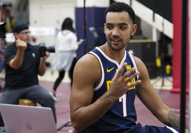 Denver Nuggets forward Trey Lyles checks over his image on a laptop as team photographer Garrett Ellwood works in the background during NBA basketball media day for the Nuggets Monday, Sept. 24, 2018, in Denver. (AP Photo/David Zalubowski)