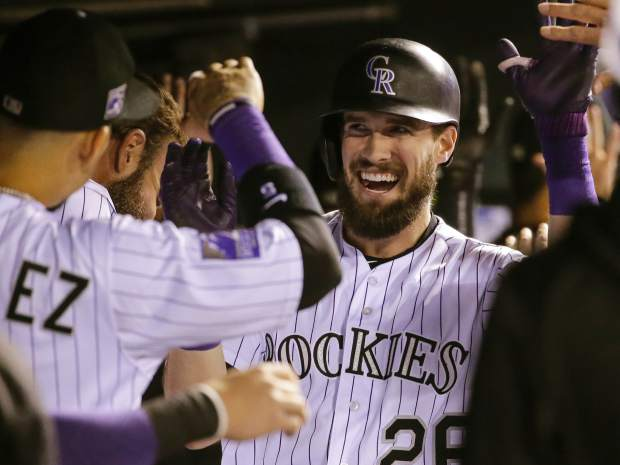 Colorado Rockies' David Dahl (26) is congratulated by teammates in the dugout after hitting a three run home run against the Philadelphia Phillies during the third inning of a baseball game on Tuesday, Sept. 25, 2018, in Denver. (AP Photo/Jack Dempsey)