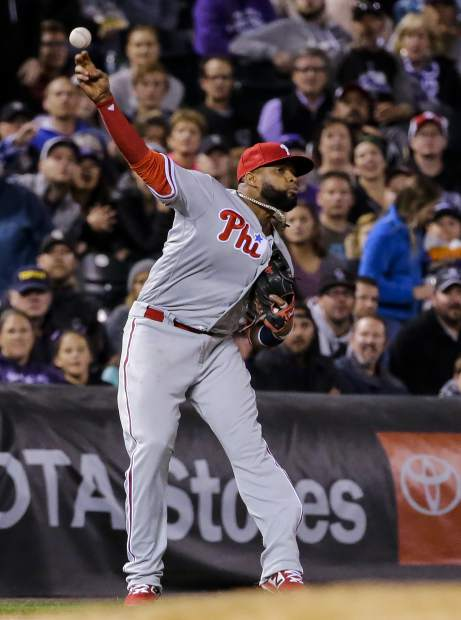 Philadelphia Phillies third baseman Carlos Santana throws to first for the out on Colorado Rockies' Trevor Story during the fourth inning of a baseball game Tuesday, Sept. 25, 2018, in Denver. (AP Photo/Jack Dempsey)