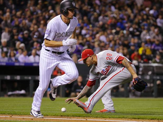 Philadelphia Phillies starting pitcher Vince Velasquez (28) scoops up a bunted ball off the bat of Colorado Rockies' Chris Rusin (52) during the fourth inning of a baseball game on Tuesday, Sept. 25, 2018, in Denver. (AP Photo/Jack Dempsey)