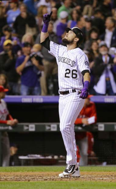 Colorado Rockies' David Dahl (26) points to the sky as he crosses home plate after hitting a three run home run against the Philadelphia Phillies during the third inning of a baseball game on Tuesday, Sept. 25, 2018, in Denver. (AP Photo/Jack Dempsey)
