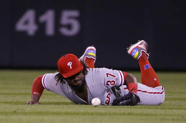 Philadelphia Phillies right fielder Odubel Herrera (37) dives but misses a pop fly hit off the bat of Colorado Rockies' Charlie Blackman during the fourth inning of a baseball game on Tuesday, Sept. 25, 2018, in Denver. (AP Photo/Jack Dempsey)