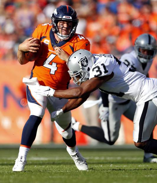 Denver Broncos quarterback Case Keenum (4) runs in for a touchdown as Oakland Raiders defensive back Marcus Gilchrist (31) defends during the second half of an NFL football game, Sunday, Sept. 16, 2018, in Denver. (AP Photo/Jack Dempsey)