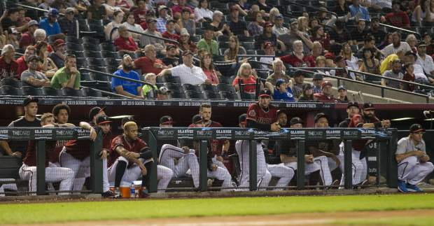 Arizona Diamondbacks players watch the last out of a basseball game against the Colorado Rockies which officially eliminated them from postseason Sunday, Sept 23, 2018, in Phoenix. (AP Photo/Darryl Webb)