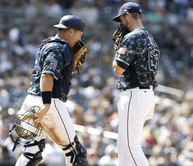 San Diego Padres catcher A.J. Ellis, left, talks with starting pitcher Jacob Nix during the sixth inning of a baseball game against the Colorado Rockies in San Diego, Sunday, Sept. 2, 2018. (AP Photo/Alex Gallardo)
