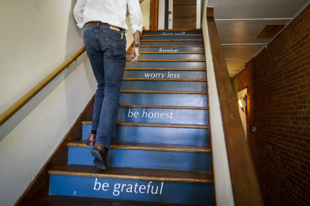 "Michael Koveleski climbs the stairs at his store Design Sleepin Yellow Springs, Ohio on Thursday, Aug. 23, 2018. ""You're only going to change your life when things are bad _ or terrible,"" Michael says. ""Our thing was 9/11, starting over with nothing. ... I am thrilled at the way it came out to be."" (AP Photo/John Minchillo)"