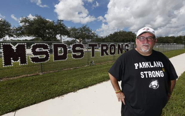 Stephen Feuerman poses for a photo in front of Marjory Stoneman Douglas High School in Parkland, Fla., on Monday, Aug. 27, 2018. Feuerman, who was working in the Empire State Building on 9/11, sold his Westchester home within months and the family moved to Parkland seeking a safer place to live and work. Seventeen years later, their two kids were in school on the day of the shooting.