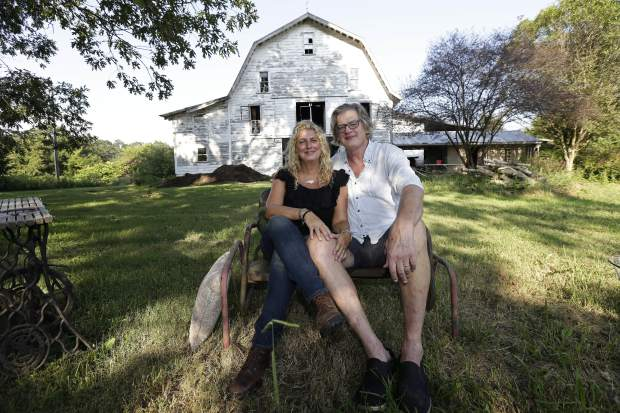 Heather and Tom LaGarde relax in the yard of their home near Saxapahaw, N.C., on Wednesday, Aug. 29, 2018. At first, the ramshackle North Carolina farm they spotted online in 2002 was only an occasional getaway from their home in Manhattan's Lower East Side neighborhood. They'd started to want one after worrying about their 1-year-old daughter's health in the 9/11 smoke. (AP Photo/Gerry Broome)